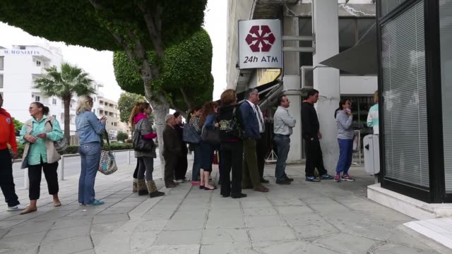 customers queue to withdraw cash from an automated teller machine atm outside a cyprus popular bank pcl also known as laiki bank in limassol 3 shots... - 列に並ぶ点の映像素材/bロール