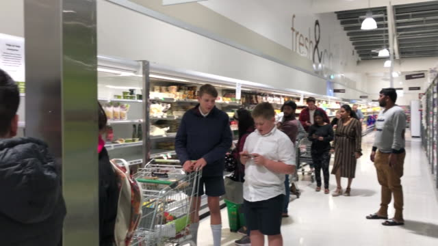 customers queuing inside supermarket to buy groceries during coronavirus crisis - new zealand stock videos & royalty-free footage