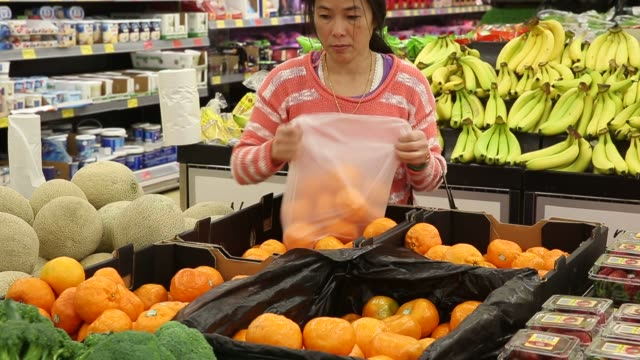 Customers shop and pick up groceries in an Aldi Stores Ltd food store in Sydney Australia on Thursday June 25 2015 Shots CU of corn flakes with...