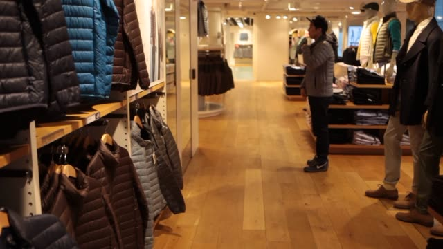 customers shop for clothes at a uniqlo co store on 5th avenue in new york us on tuesday jan 21 wide shot of customers walking into uniqlo and being... - flagship store stock videos and b-roll footage