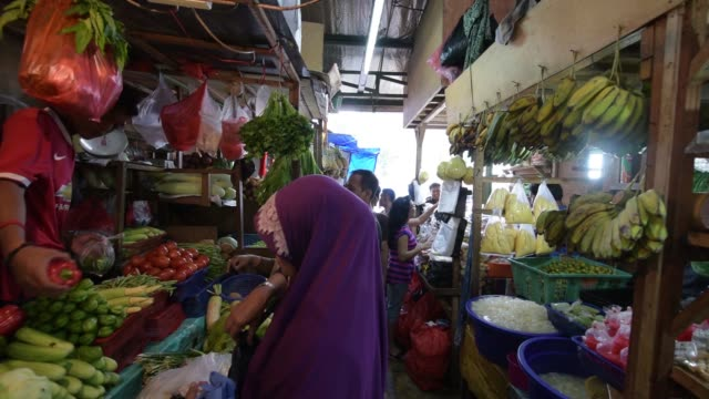 vídeos de stock e filmes b-roll de customers shop for vegetables at a stall at the pasar induk kramat jati market in jakarta, indonesia, on sunday, june 21 customers browse vegetables... - lagenaria