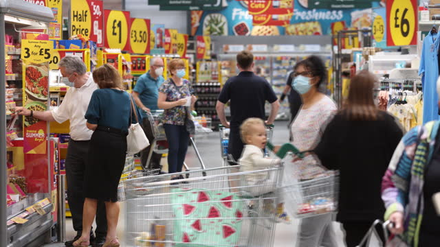 customers shopping at morrisons supermarket wearing protective face masks in st. ives, cambridgeshire, u.k., on monday, july 5, 2021. - groceries stock videos & royalty-free footage