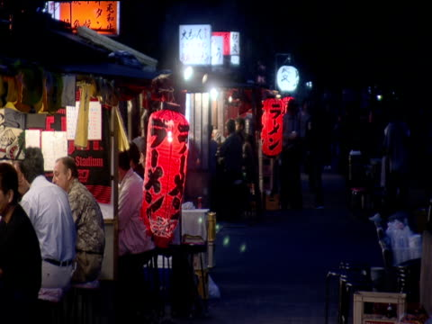 stockvideo's en b-roll-footage met customers sit at yatai food stalls lined up along pavement fukuoka - 1990 1999