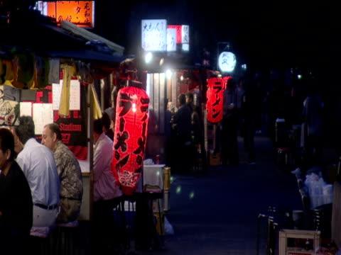 vídeos y material grabado en eventos de stock de customers sit at yatai food stalls lined up along pavement fukuoka - 1990 1999