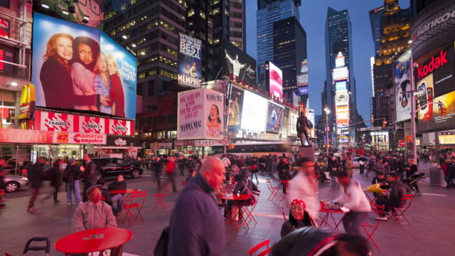 Customers sit down to eat at small tables underneath the neon lights and billboards of Times Square, New York.