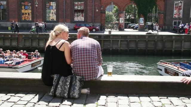 Customers sit eating meals at outdoor restaurant tables in the Nyhavn district of Copenhagen Denmark on Tuesday June 24 Back view a young couple sit...