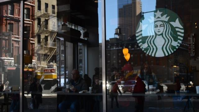customers sit inside a starbucks corp location in new york us on wednesday jan 22 wide shot of customers wearing winter coats sit inside a starbucks... - スターバックス点の映像素材/bロール