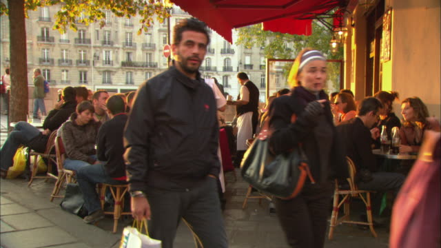 vidéos et rushes de ws customers sitting at busy cafe on sidewalk, paris, france - paris