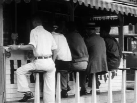 b/w 1930 rear view 5 customers sitting on stools at outdoor lunch counter / los angeles, ca - 1930 stock-videos und b-roll-filmmaterial