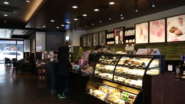 vídeos de stock, filmes e b-roll de customers stand at a counter inside astarbuckscoffee korea co store in gimpo south korea interiors of a starbucks location in gimpo south korea... - starbucks