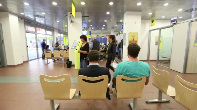 customers stand at booths as others wait to be served by employees inside a poste italiane spa post office in rome italy on wednesday 7 october 2015... - post office stock videos & royalty-free footage
