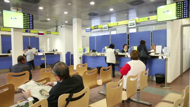 customers stand at booths as others wait to be served by employees inside a poste italiane spa post office in rome italy on wednesday 7 october 2015... - ufficio postale video stock e b–roll