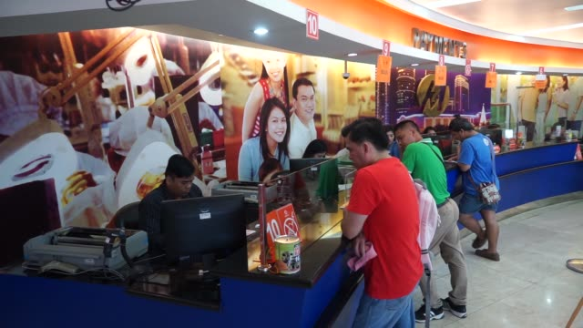 Customers stand in line at a service counter at the Manila Electric Co business center in the Makati district of Manila the Philippines on Thursday...