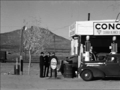 "b/w 1934 pan customers standing near ""conoco"" desert gas station / sierra blanca, texas - 1934 stock-videos und b-roll-filmmaterial"