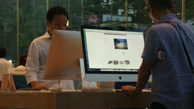 customers try apple inc products displayed inside the companys omotesando store in tokyo japan on friday june 13 2014 customers try apple inc imac... - apple computer stock-videos und b-roll-filmmaterial