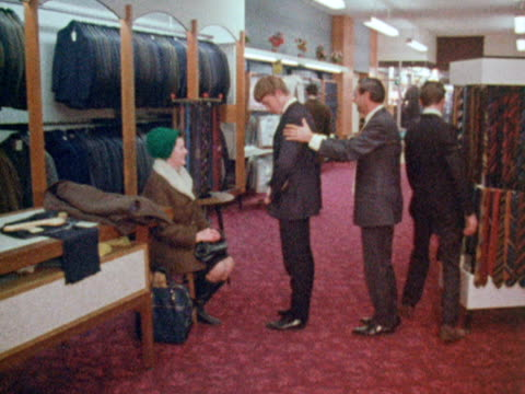 Customers try on suits in a menswear shop