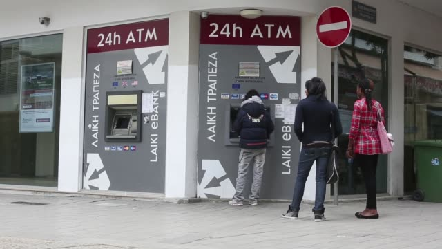 Customers use 24hour automated teller machines operated by Laiki Bank also known as Cyprus Popular Bank Plc in Nicosia Sticker in wal advertising...