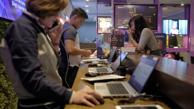 Customers use smartphones while waiting to be assisted at a service desk inside a Globe Telecom Inc Iconic store in Manila the Philippines on Monday...