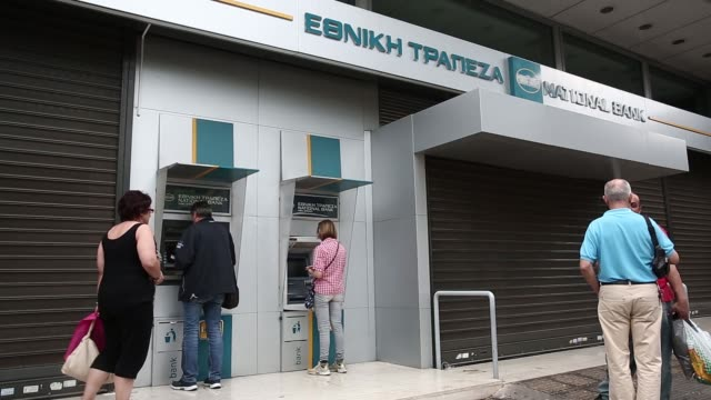 Customers uses automated teller machines outside a National Bank of Greece SA bank branch in Athens Greece on Monday June 29 2015