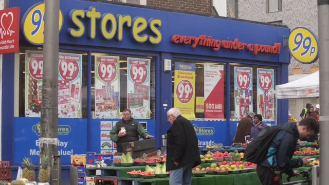 customers visit a fruit stall outside a 99p store in walthamstow on friday, november 21 wide of the store - financial item stock videos & royalty-free footage