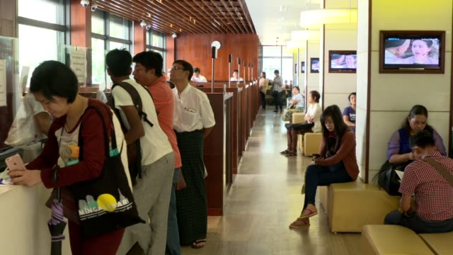 Customers walk past a reception counter inside a Kanbawza Bank Ltd bank branch in Yangon Myanmar on Wednesday March 8 Bank employees assist customers...