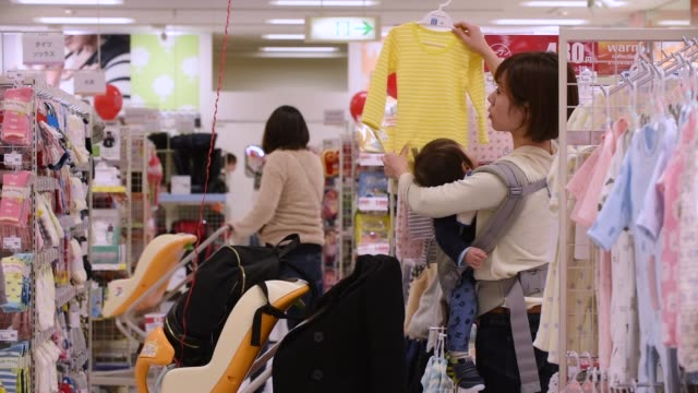 Customers walk past aisles at the Ito Yokado Co Ario shopping center owned by Seven i Holdings Co during its reopening in Tokyo Japan on Friday Nov...