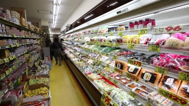 customers walk through a supermarket in tokyo shoppers browse vegetables at a supermarket in tokyo tracking shot down a supermarket aisle stopping at... - 生鮮食品コーナー点の映像素材/bロール