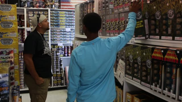 vídeos y material grabado en eventos de stock de customers walk through aisles of fireworks products inside a fireworks store in jasper, tennessee on june 29th, 2015 shots: shoppers walk through the... - firework explosive material