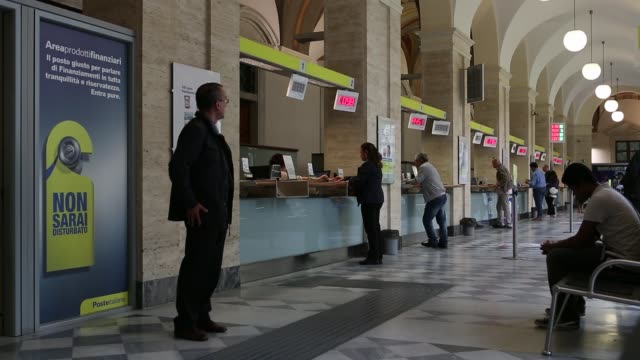 customers walk through corridor at entrance to a poste italiane spa post office in rome customers are served at counters inside post office customers... - post office stock videos & royalty-free footage