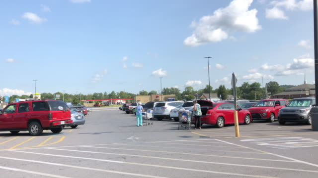 customers wearing face mask pushing shopping carts in walmart shopping center parking lot in north georgia, usa amid the 2020 global coronavirus pandemic - parking stock videos & royalty-free footage