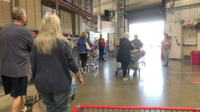 customers wearing face mask pushing shopping carts leaving costco wholesale store amid the global coronavirus pandemic. - catena di negozi video stock e b–roll