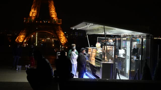 customers wearing protective face masks are ordering food at a street food truck at place du trocadero near the eiffel tower during night time on... - ordering stock videos & royalty-free footage