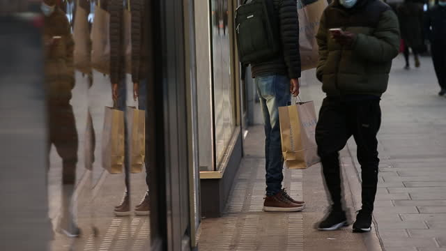 customers with shoping bags walking along oxford street in city of london, london, england, u.k., on wednesday, december 2, 2020. most of england's... - shopping bag stock videos & royalty-free footage