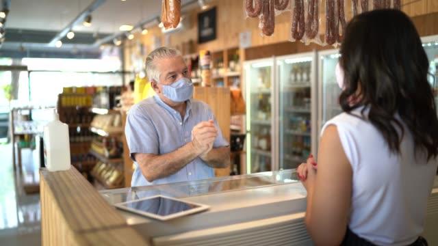 vídeos de stock, filmes e b-roll de cliente usando desinfetante para as mãos e comprando alguns frios com um açougueiro - usando máscara facial - cumprimentando