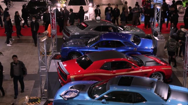 Customized vehicles stand on display at the Tokyo Auto Salon in Chiba Japan on Friday Jan 12 Attendees walk past vehicles displayed at the Tokyo Auto...