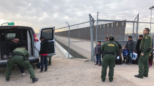 customs and border patrol agents talk to central american immigrants at the u.s.-mexico border fence on february 01, 2019 in el paso, texas. the... - 国境点の映像素材/bロール
