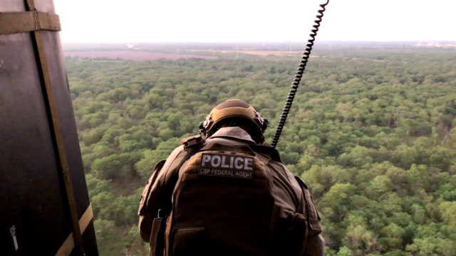 A US Customs and Border Protection agent searches for undocumented immigrants during a dusk helicopter patrol over the Rio Grande at the USMexico...