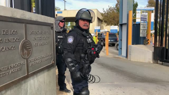 US Customs and Border Protection agents stand on the US side of the USMexico border marker at the San Ysidro port of entry during a 'largescale...