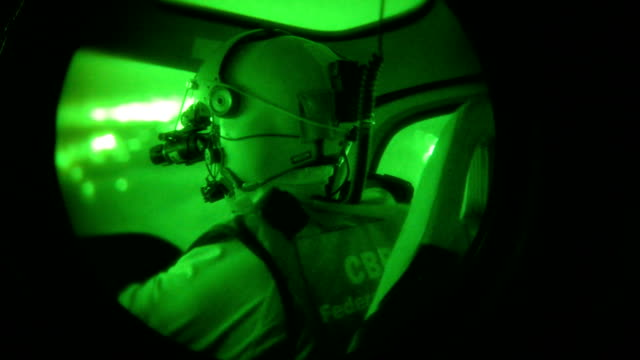 a us customs and border protection helicopter crew searches for undocumented immigrants while flying a night patrol with nightvision goggles over the... - night vision stock videos and b-roll footage