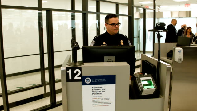 customs and border protection officers use facial recognition technology in their booths at miami international airport to screen travelers entering... - 将校点の映像素材/bロール