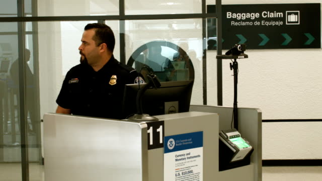 Customs and Border Protection officers use facial recognition technology in their booths at Miami International Airport to screen travelers entering...