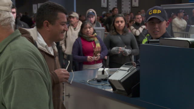 / customs border protection officer checking documents of people entering us - zoll und einwanderungskontrolle stock-videos und b-roll-filmmaterial