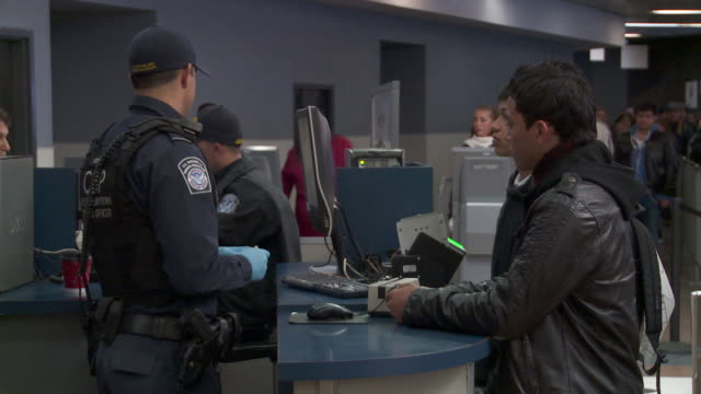 / customs & border protection officer checking documents of people entering us - looking over stock videos & royalty-free footage