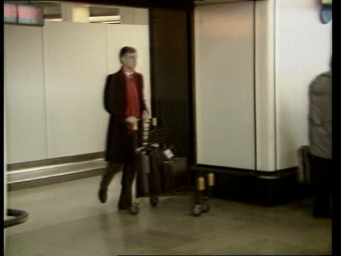 customs officers strike; itn england: london: heathrow airport: int passengers carrying luggage l-r out of customs area cms passengers towards... - bag stock videos & royalty-free footage