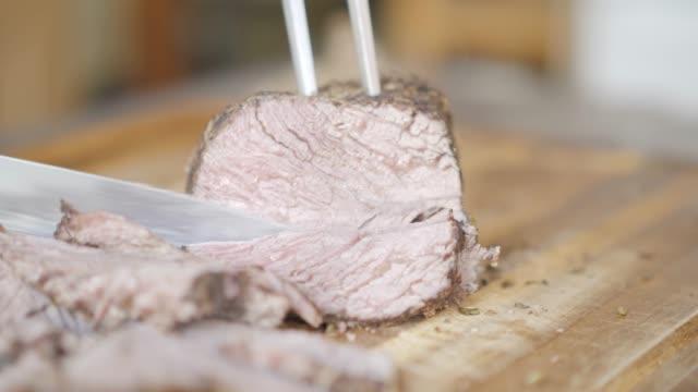 vidéos et rushes de coupe de boeuf rôti sur planche à découper en bois - aliment en portion