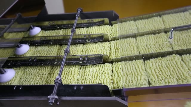 vídeos de stock, filmes e b-roll de cut squares of instant noodles move along a conveyor in trays, noodles are arranged by machine on a conveyor, an employee arranges packets of soup on... - doces