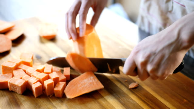 cut sweet potato into cubes at kitchen - chopped stock videos and b-roll footage