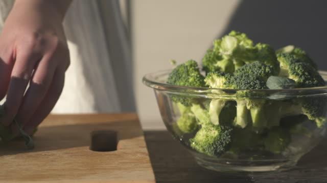 cut the fresh broccoli with a knife. - schüssel stock-videos und b-roll-filmmaterial