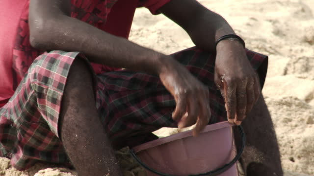 cutaway of beninese fisherman with hands in bucket - cutaway video transition stock videos & royalty-free footage