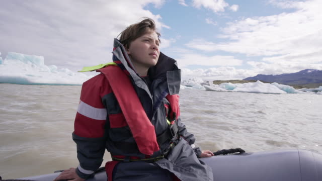 cute 10 years old boy enjoys a rubber boat trip on fjallsárlón glacier lake in iceland - pre adolescent child stock videos & royalty-free footage